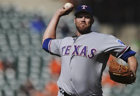 Texas Rangers starting pitcher Colby Lewis works the second inning against the Baltimore Orioles in their first game of a doubleheader durin