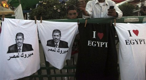 "A boy stands near t-shirts with images of elected president Mohamed Mursi and words that read ""Congratulations to Egypt"" that are sold durin"