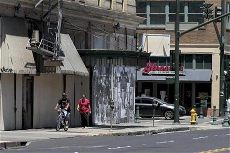 People walk past shuttered businesses in downtown Stockton, California June 27, 2012. REUTERS/Kevin Bartram