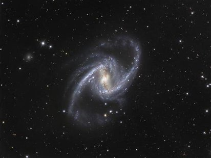 The NGC 1365 galaxy, also known as the Great Barred Spiral Galaxy, is seen in an image that combines observations performed through three di