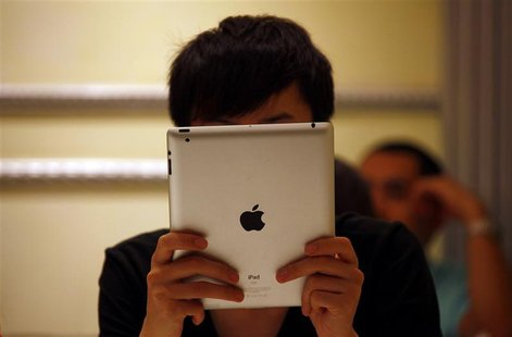 A man looks at his iPad while sitting in a cafe in central Beijing June 6, 2012. Apple Inc is looking to open flagship stores in the major C