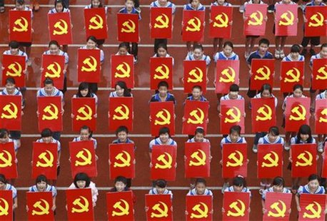 Middle school students hold cardboards featuring the emblems of the Communist Party of China as they pose for photographs during an event to