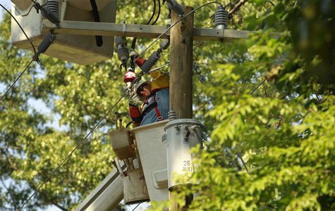 A lineman works to restore power to a neighborhood of Falls Church, Virginia July 3, 2012. REUTERS/Kevin Lamarque