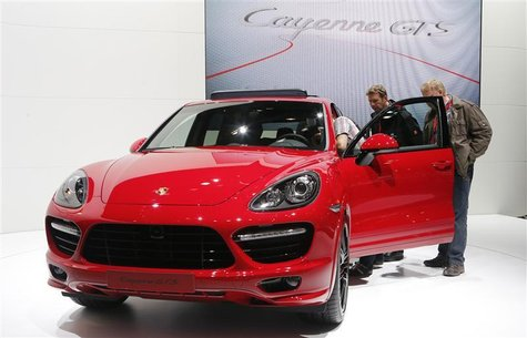 People watch a Porsche Cayenne GTS car during a press preview day at the AMI Auto Show in Leipzig June 1, 2012. The show opens to the public