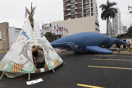 Protesters demonstrate next to an inflatable whale and a teepee with painted whales and dolphins outside the building where the Internationa