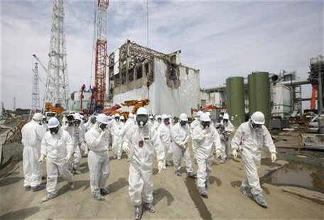 Members of the media and Tokyo Electric Power Co. (TEPCO) employees, wearing protective suits and masks, walk in front of the No. 4 reactor