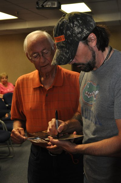 Guest Jim Scheel gets an autographed CD from Rick Monroe