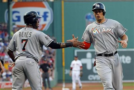Miami Marlins Jose Reyes (L) and Giancarlo Stanton congratulate each other after scoring against the Boston Red Sox in the first inning of t
