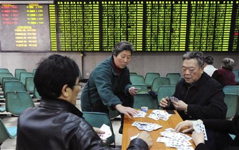 Investors play cards in front of an electronic board showing stock information filled with green-coloured figures, which indicate falling pr