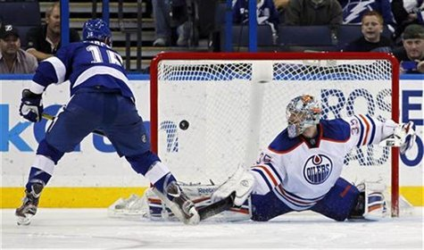 Tampa Bay Lightning's Teddy Purcell (L) shoots past Edmonton Oilers goalie Nikolai Khabibulin during the shootout in their NHL hockey game i