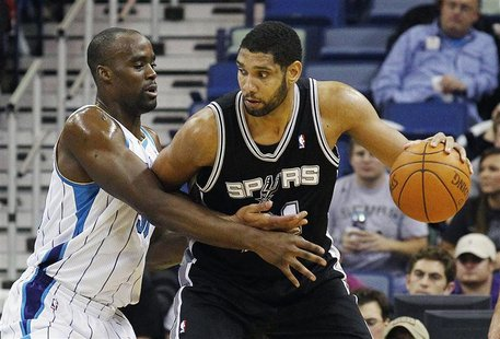 San Antonio Spurs center Tim Duncan (R) works against New Orleans Hornets center Emeka Okafor during the first half of their NBA basketball