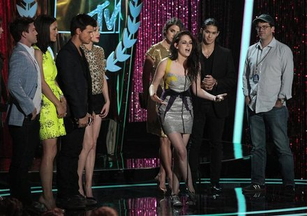 "Actress Kristen Stewart (C) accepts the award for movie of the year for ""The Twilight Saga: Breaking Dawn Part 1"" at the 2012 MTV Movie Awar"