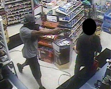 An armed robber points a gun at a clerk in the Family Fare gas station on Washington Ave. around 10:30 PM on July 12, 2012. (photo courtesy Holland Dept. of Public Safety)