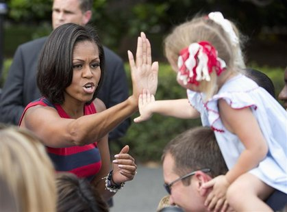 First Lady Michelle Obama high-fives a child during Independence Day celebrations on the South Lawn of the White House in Washington July 4,