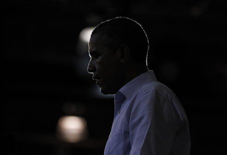 U.S. President Barack Obama is silhouetted during a campaign rally at Phoebus High School in Hampton, Virginia, July 13, 2012. REUTERS/Jason