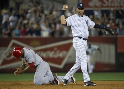 New York Yankees shortstop Derek Jeter and Los Angeles Angels runner Howard Kendrick (L) react after Jeter caught Kendrick trying to steal s