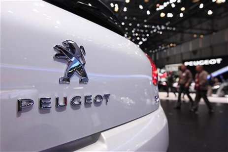 Visitors walk on the Peugeot booth during the second media day of the 82nd Geneva Car Show at the Palexpo Arena in Geneva March 7, 2012. The
