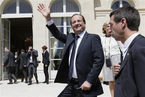 France's President Francois Hollande waves to visitors in the gardens of the Elysee Palace in Paris July 14, 2012. REUTERS/Kenzo Tribouillar