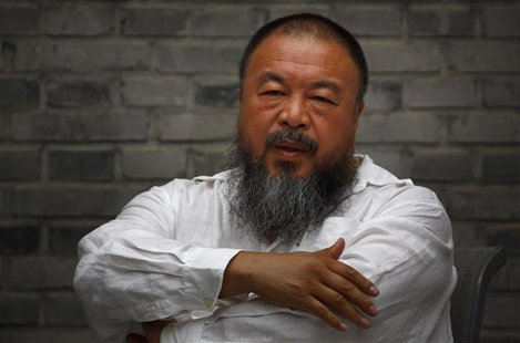 Chinese dissident artist Ai Weiwei folds his arms as he sits on a chair in the courtyard of his studio in Beijing June 20, 2012. REUTERS/Dav