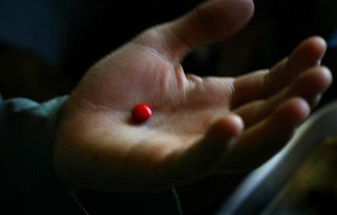 A malnourished boy holds an iron supplement pill in his palm before swallowing it at a supplementary feeding clinic in Kohistan, about 50 km