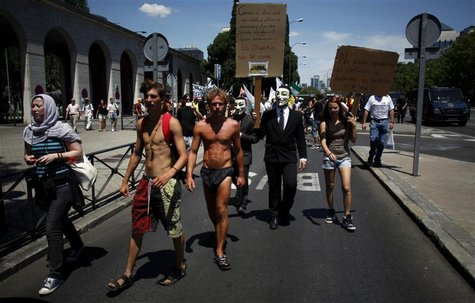 Demonstrators wearing Guy Fawkes masks march outside the Spanish Labour Ministry during an unemployment protest in Madrid July 21, 2012. REU