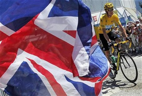 Sky Procycling rider and leader's yellow jersey Bradley Wiggins of Britain cycles past a British flag as he prepares to start before the ele