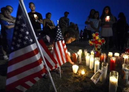 Myia Young, 4, places a candle by an American flag during a vigil for victims behind a theater where a gunman open fire at moviegoers in Aurora, Colorado July 20, 2012.  Credit: REUTERS/ Jeremy Papasso