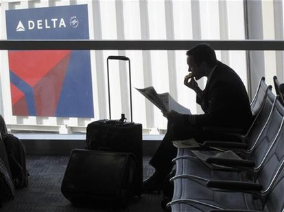 A passenger waits for his flight near a Delta Air Lines logo at Detriot Airport November 20, 2010. REUTERS/Sim Wei Yang