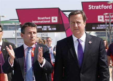 Britain's Prime Minister David Cameron (R) walks with Chairman of the Olympic organising committee (LOCOG) Sebastian Coe at the Olympic Park
