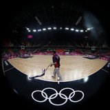 A worker sweeps the court before a training session at the Basketball Arena before the start of the London 2012 Olympic Games July 26, 2012.