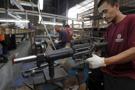 A former illegal gunsmith inspects a newly assembled multi-action shotgun at Shooters Arms, a gun manufacturing company exporting different