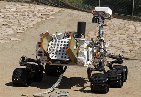 An engineering model of NASA's Curiosity Mars rover is seen from the rear in a sandy, Mars-like environment named the Mars Yard at NASA's Je