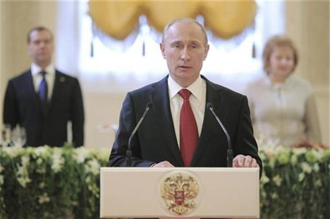 Russia's new President Vladimir Putin (front) speaks during a reception, dedicated to the start of his term as Russia's new President, with