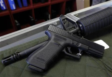 A Glock 22 pistol is seen laying on a Palmetto M4 assault rifle at the Rocky Mountain Guns and Ammo store in Parker, Colorado July 24, 2012.