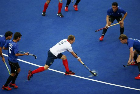 Britain's Daniel Fox (C) dribbles surrounded by Argentina's players during their men's Group A hockey match at the London 2012 Olympic Games