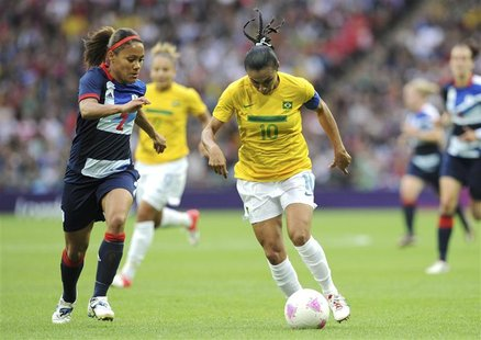Brazil's Marta (R) dribbles the ball against Britain's Alex Scott during their women's Group E football match at the London 2012 Olympic Gam