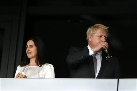 London mayor Boris Johnson (R) sips wine as his wife Marina Wheeler stands to his left in the VIP box before the opening ceremony of the Lon