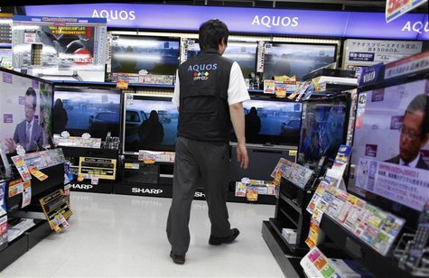 A salesperson walks among Sharp Corp's Aquos liquid-crystal display (LCD) televisions displayed at an electronic store in Tokyo in this June