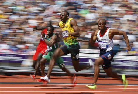 Usain Bolt (C) of Jamaica runs on his way to winning his 100m heat round 1 during the London 2012 Olympic Games at the Olympic Stadium Augus