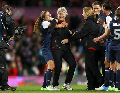 USA's Alex Morgan (L) celebrates with her coach Pia Sundhage after defeating Canada in the women's semi final soccer match at the London 201