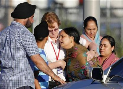 A distraught women is helped to a car outside of the Sikh temple in Oak Creek, Wisconsin August 5, 2012. REUTERS/Tom Lynn