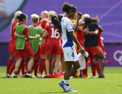 France's Laura George (4) walks off the pitch as Canada celebrates winning the women's bronze medal soccer match in Coventry at City of Cove