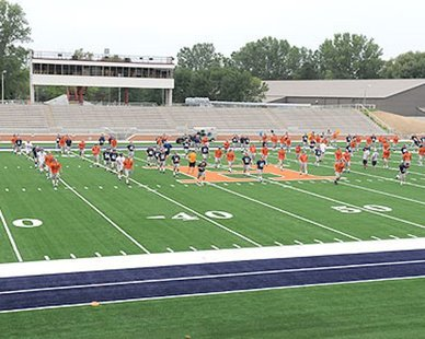 Coach Dean Kreps puts his Hope College football team through their paces in the first workout on the new artificial playing surface at Holland Municipal Stadium on Aug. 9, 2012. (photo courtesy Hope College)