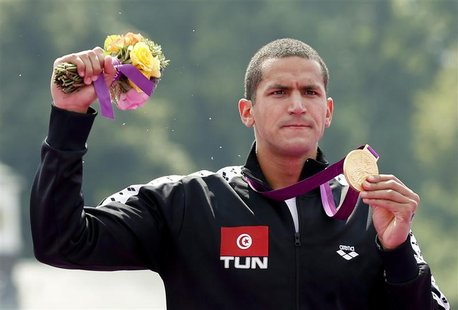 Tunisia's Oussama Mellouli poses with his gold medal after the men's 10km marathon swimming at Hyde Park during the London Olympic Games Aug