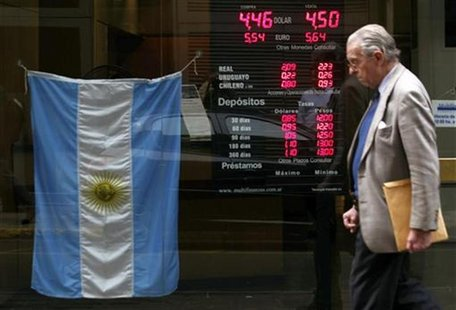 A man walks past an electronic board showing currency exchange rates and an Argentine flag at a money exchange in Buenos Aires, June 1, 2012