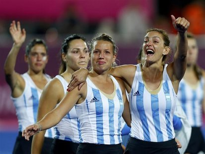 Argentina's Luciana Aymar (R) with team mates greets spectators after being defeated by Netherlands during their women's gold medal hockey m