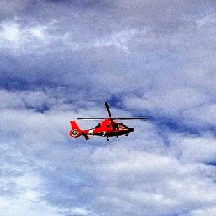 A Coast Guard Helicopter flies above lake Michigan searching for two missing men Friday afternoon (Photo: Jon MacDonald)