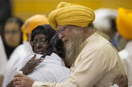 Family members and mourners fight their emotions during a wake and visitation service for victims of last Sunday's attack at a Sikh temple, at Oak Creek High School, in Oak Creek, Wisconsin August 10, 2012.