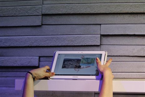 A Samsung employee reaches up to display a Samsung Galaxy Note 10.1 at an unveiling event in New York August 15, 2012. REUTERS/Lucas Jackson