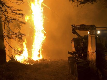 A U.S. Forest Service equipment trailer is seen beside a wildfire at the Springs Fire in Boise National Forest near Banks-Garden Valley, Ida